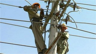 Workers on an electricity pylon in Pakistan