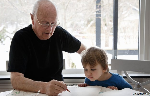 Image of a man helping his grandson with homework