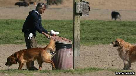 A man putting a dog poo bag in a bin