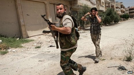 Syrian rebel fighters belonging to the Martyrs of Maaret al-Numan battalion leave their position after a range of shootings on 13 June 2013 in Maaret al-Numan