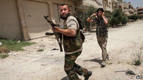 Syrian rebel fighters belonging to the Martyrs of Maaret al-Numan battalion leave their position after a range of shootings on 13 June 2013 in Maaret al-Numan
