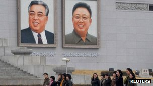 North Korean women walk in front of portraits of North Korea's founder Kim Il-sung (L) and late leader Kim Jong-il at Kim Il-sung Square in Pyongyang, 1 April 2013