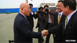 Japanese Cabinet Secretariat Advisor Isao Iijima (left) shakes hands with North Korean officials as he arrives at Pyongyang airport, 14 May 2013