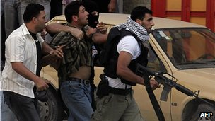 Palestinians from the Fatah-linked Al-Aqsa Martyrs' Brigades arrest an alleged Hamas member in the West Bank city of Nablus, 14 June 2007