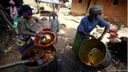A woman and her daughter work on extracting oil from palm seeds in Dabou,  Ivory Coast
