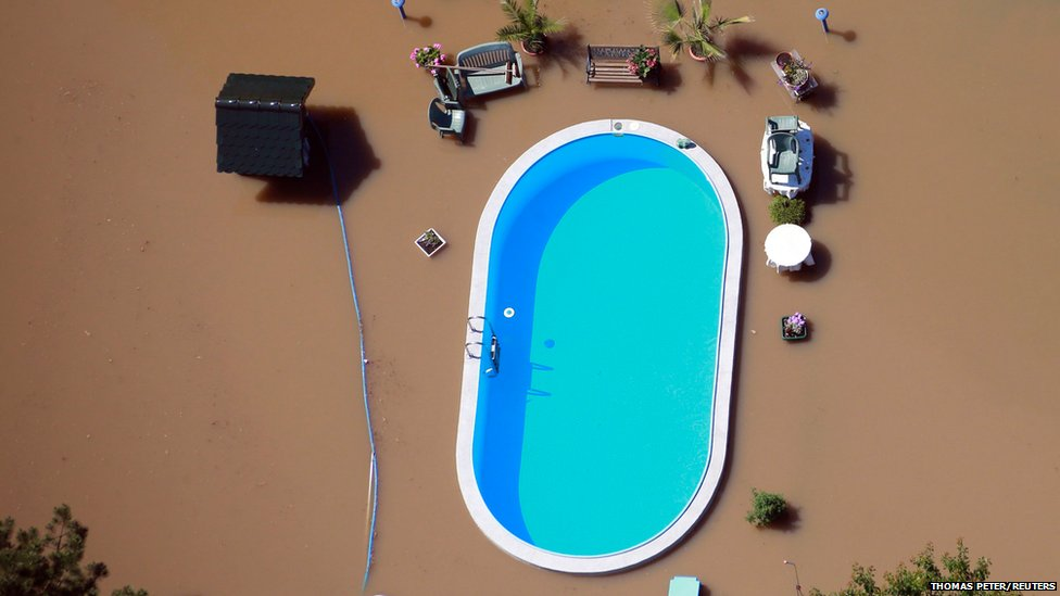 Garden with a swimming pool is inundated by the waters of the elbe