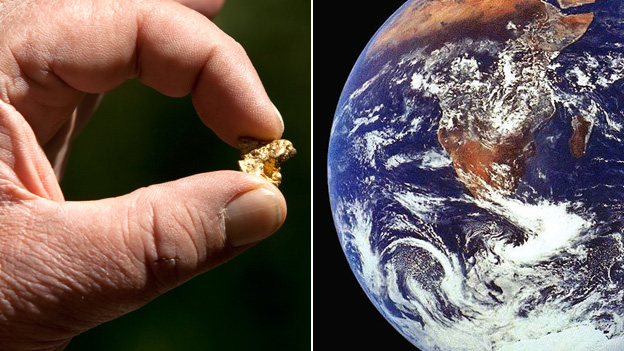 A man holding a nugget of gold and the planet earth