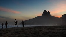 Brazilians play football on a beach in Rio de Janeiro