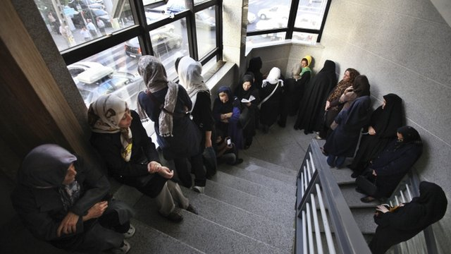 Iranian women queue in a polling station to vote