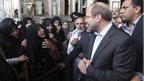 Tehran Mayor and Iranian presidential candidate, Mohammad Bagher Qalibaf, listens to women as he arrives at a polling station for the presidential election in Tehran, June 14. He also has a high-profile wife with her own political identity.