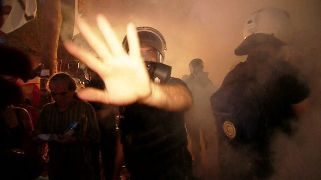 Riot police waving away camera through fog of tear gas