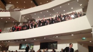 Politicians, waiting for the president, perform a   Mexican wave in the auditorium.