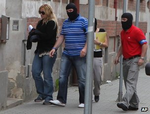 Masked Czech police officers escort the prime minister's chief of staff, Jana Nagyova, to a police station in Ostrava, 14 June