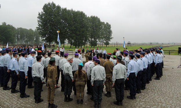 Soldiers stand to attention around the Israeli flag