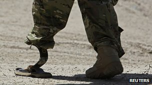 A Nato soldier walks with an artificial limb to board a Chinook helicopter after a security handover ceremony at a military academy outside Kabul, 18 June 2013