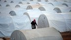 An internally displaced Syrian man walks amidst tents in the Maiber al-Salam refugee camp along the Turkish border