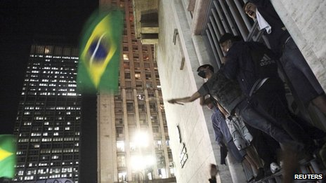 Demonstrators climb up the entrance gates of City Hall in Sao Paulo