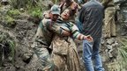 An Indian army personnel carries a stranded woman pilgrim to a safer area in Chamoli district, in the northern Indian state of Uttarakhand, India, Tuesday, June 18, 2013