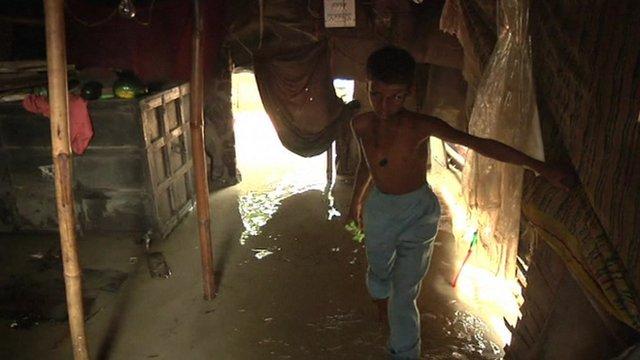 A boy wades through flood water
