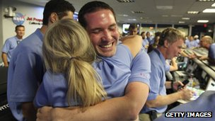 NASA colleagues hugging and cheering