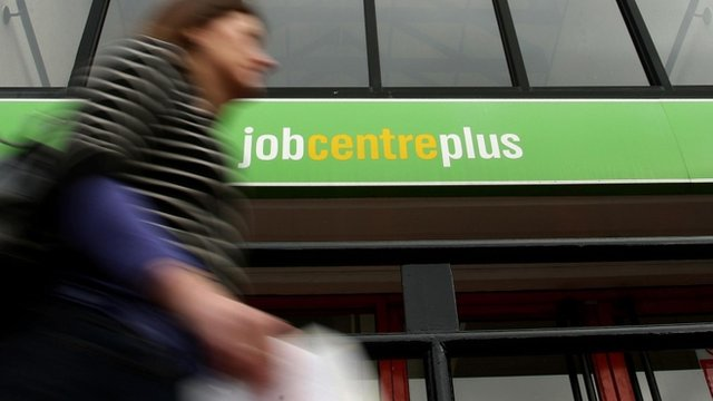 A woman walks past a Job Centre sign