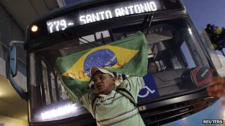 A man holding a Brazilian national flag stands in front of a bus during a protest in Brasilia