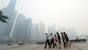 Office workers return from a lunch break in front of buildings blanketed by haze in Singapore on 19 June 2013