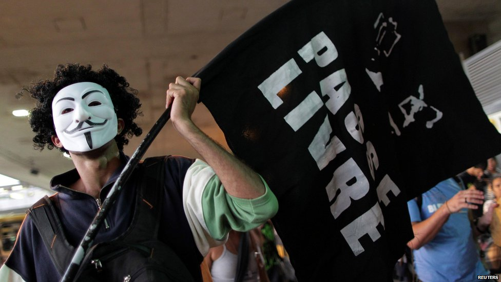 "Protester wearing a Guy Fawkes mask and carrying the banner of the ""Free Pass"" movement (19 June)"