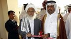 A Qatari official, center right, and Taliban official Jan Mohammad Madani, center left, cut the ribbon at the official opening ceremony of a Taliban office in Doha