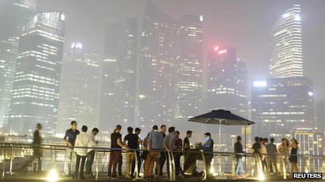 Partygoers line up to enter a nightclub at Marina Bay Sands, as haze shrouds the skyline of Singapore in the background on 19 June 2013