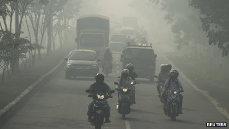 Motorists travel through haze in Pekanbaru, Indonesia's Riau province on 20 June 2013