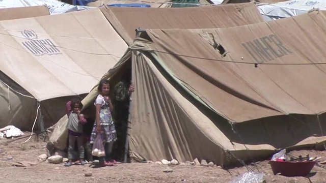 Refugee children outside a tent