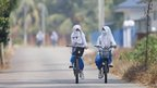 Students, one wearing a face mask and the other covering her mouth with her headscarf, leave for home after an early dismissal from school due to the haze in Muar, in Malaysia's southern state of Johor bordering Singapore, 20 June 2013