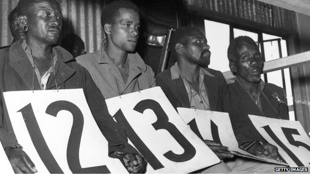 14 April 1953: Suspected members of the Mau Mau, accused of murder on trial. They are sitting in a shed holding large identifying numbers on their laps