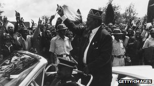 Kenyan politician Jomo Kenyatta waving to cheering crowds during Kenya independence day celebrations in 1963
