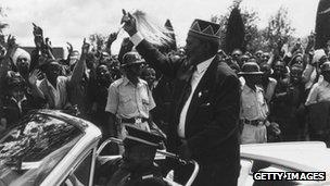 Kenyan politician Jomo Kenyatta waving to cheering crowds during Kenya independence day celebrations in 1963