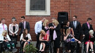 Mourners in wheelchairs outside the church