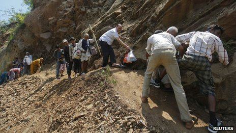 Pilgrims try to cross a pathway damaged by landslide Rudraprayag in the Himalayan state of Uttarakhand June 20, 2013.