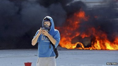 A protester uses a mobile phone as he passes next to a burning vehicle during a protest at Taksim Square in Istanbul (11 June 2013)