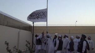 Taliban members raise the group's flag at the office in Doha