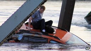 A man is seen sitting atop a car that fell into the Skagit River after the collapse of the Interstate 5 bridge there minutes earlier 23 May 2013