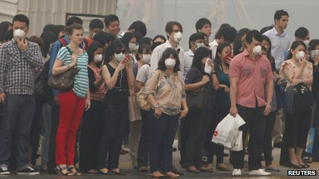 Office workers wearing masks wait to cross a road in Singapore on 21 June 2013