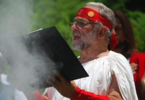 Tryphon Olympios reading from a book with smoke rising around him