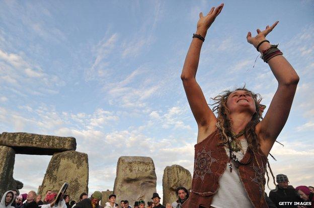 A woman at Stonehenge celebrates summer solstice