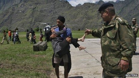 A man carries a flood victim after they were rescued by the army in Uttarakhand on June 19, 2013