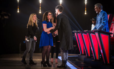Danny congratulating Andrea, with a member of the production staff waiting to guide her from the stage
