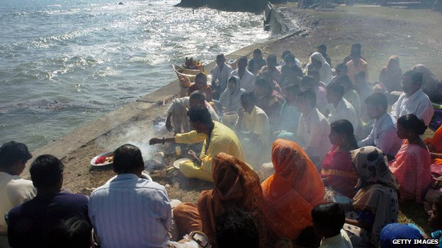 Hindu devotees worship the sun god by the sea