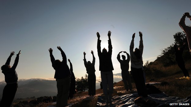 People are practicing yoga at the megalithic observatory of Kokino, in Macedonia