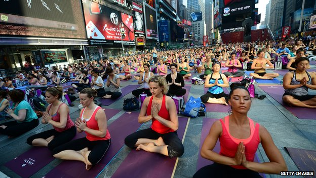 Numerous people practicing yoga in Times Square, New York City