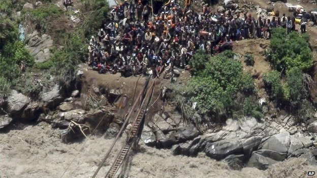 Rescuers attempting to use makeshift bridges to help stranded pilgrims in India